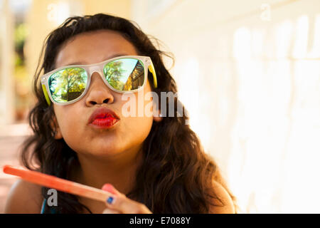 Portrait of girl with red lips and ice lolly stick pulling face