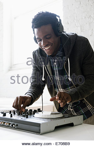 DJ using mixing desk - Stock Photo