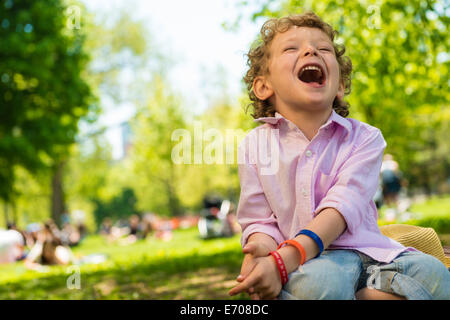 Boy sitting laughing in park - Stock Photo