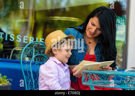 Young mother reading story book with son at sidewalk cafe - Stock Photo