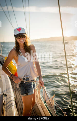 Portrait of young woman standing on boat - Stock Photo