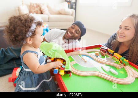 Mother and father playing with young daughter, train set on table - Stock Photo