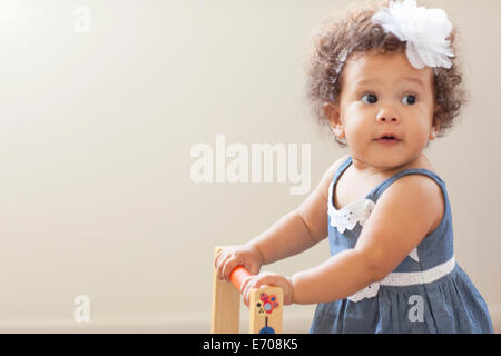Portrait of baby girl, pushing baby walker - Stock Photo