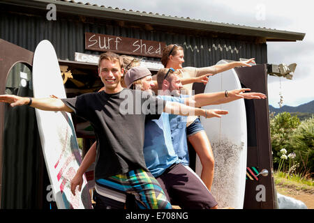 Group portrait of five young adult surfer friends posing with arms outstretched - Stock Photo