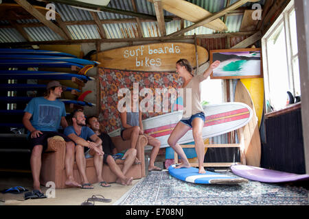 Five young adult surfer friends fooling around in surf shed - Stock Photo