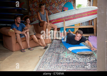 Four young adult surfer friends messing around in surf shed - Stock Photo