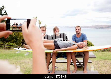 Young woman photographing surfer friends with smartphone - Stock Photo