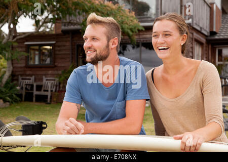 Young surfer couple with surfboard on lap - Stock Photo