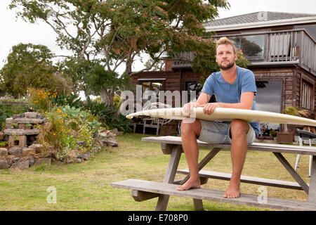 Portrait of male surfer sitting on picnic bench with surfboard on lap - Stock Photo