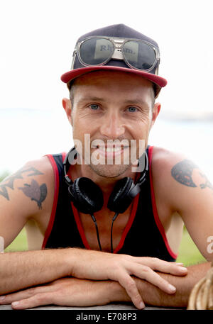 Portrait of smiling mid adult man wearing baseball cap at coast - Stock Photo