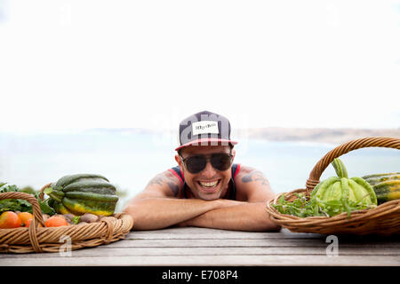 Portrait of mid adult man in baseball cap and shades leaning forward on picnic bench - Stock Photo