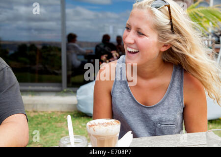 Young woman sitting at picnic bench drinking glass of latte - Stock Photo