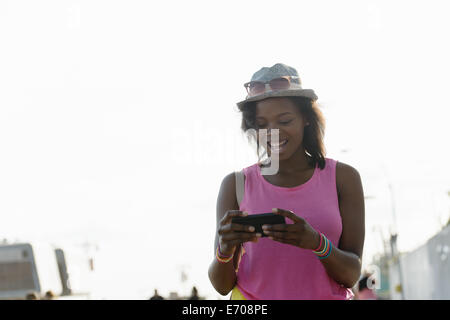 Young woman looking at smartphone, Coney Island, Brooklyn, New York, USA - Stock Photo
