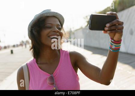 Young woman taking selfie on smartphone, Coney Island, Brooklyn, New York, USA - Stock Photo