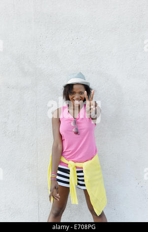 Portrait of young woman making peace sign in front of wall, Coney Island, Brooklyn, New York, USA - Stock Photo