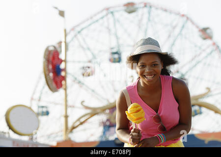 Portrait of young woman with ice cream cone, Coney Island, Brooklyn, New York, USA - Stock Photo