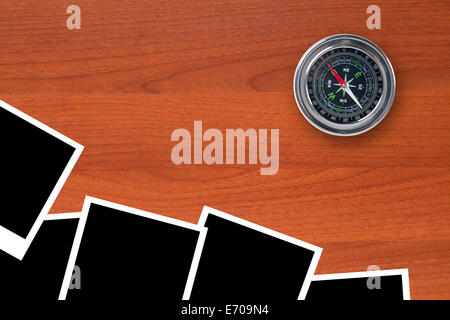 Blank, black picture frames with compass on wooden table. - Stock Photo