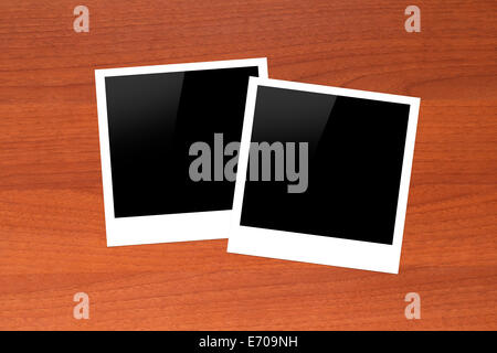 Blank, black picture frames with copy space on wooden table. - Stock Photo