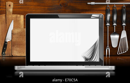 Black and metallic laptop computer with blank pages in a kitchen with cutting boards and utensils on wooden wall. - Stock Photo