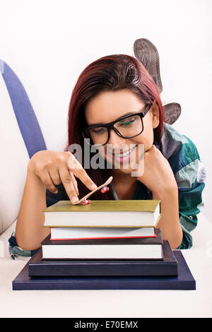 Young girl lying on a bed, playing with toy skateboard on a stack of books. - Stock Photo