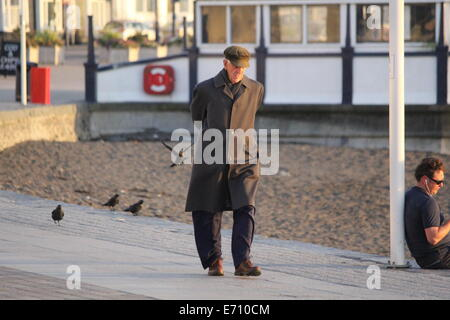 AN ELDERLY MAN TAKES AN EVENING WALK PAST THE BANDSTAND IN ABERYSTWYTH - Stock Photo