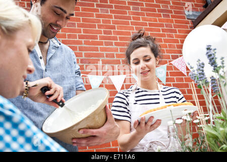 Three friends preparing fruit flan and meringue at garden party - Stock Photo