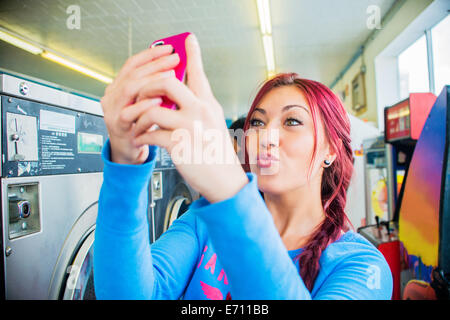 Young woman in laundromat, taking self portrait with smartphone - Stock Photo