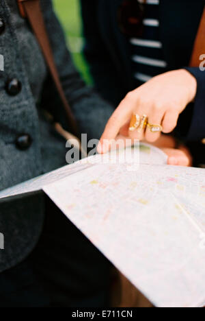 Two people using a map or guide book to find their way around a city. - Stock Photo