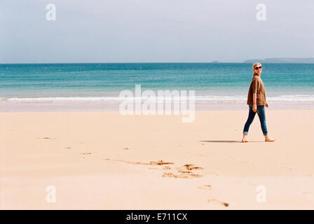 A woman walking barefoot on a beach, leaving footprints in the sand. - Stock Photo