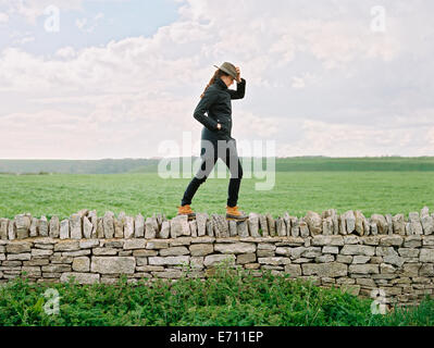 A woman in a hat walking along the top of a dry stone wall in a field. - Stock Photo