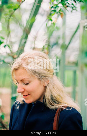 A blonde haired woman in a conservatory or tropical plant house. - Stock Photo