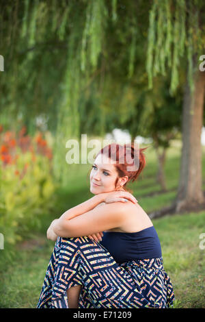 A woman sitting under a weeping willow tree. - Stock Photo