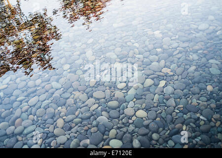 Pebbles on a river bed. Reflections and ripples on the surface. - Stock Photo