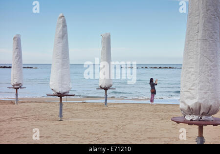 Young woman photographing sea with smartphone, Pescara, Abruzzo, Italy - Stock Photo
