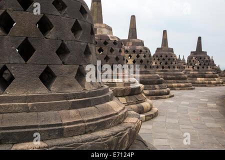 Borobudur, Java, Indonesia.  Stupas on the upper level of the temple.  The diamond-shaped holes symbolize the passions. - Stock Photo