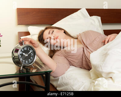 Sleepy young woman switching off alarm clock from bed - Stock Photo