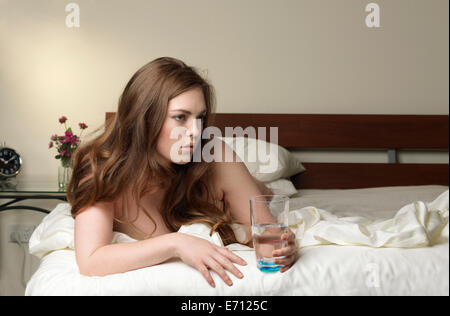 Sullen young woman with glass of water on hotel bed - Stock Photo