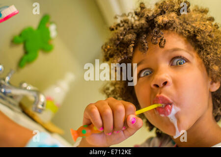 Portrait of girl pulling face whilst brushing teeth - Stock Photo