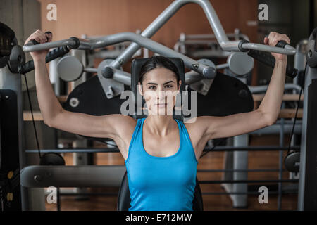 Young woman using weight equipment - Stock Photo