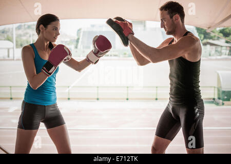 Young woman boxing with personal trainer - Stock Photo