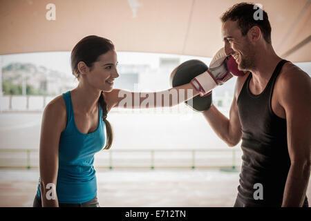 Young woman wearing boxing glove touching man's face - Stock Photo