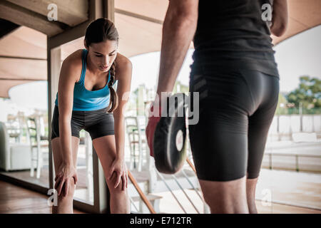 Young woman bending forwards, resting - Stock Photo