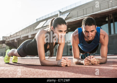 Man and woman doing plank exercises - Stock Photo
