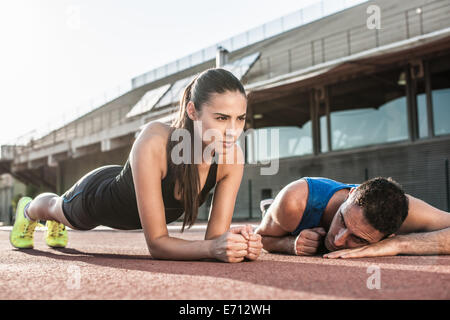 Woman doing plank exercise, man resting on floor - Stock Photo