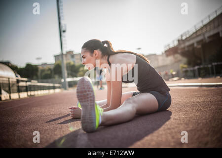 Woman sitting on floor stretching legs - Stock Photo