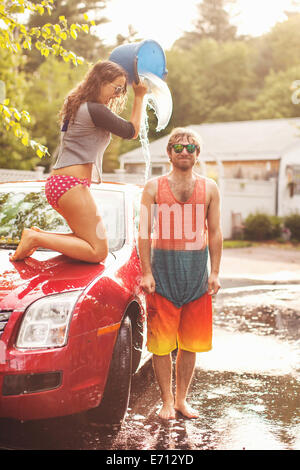 Young woman pouring bucket of water on man's head - Stock Photo