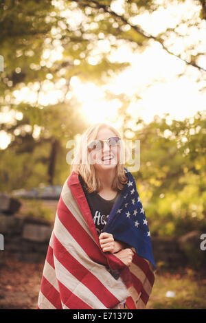 Young woman wrapped in US flag, portrait - Stock Photo