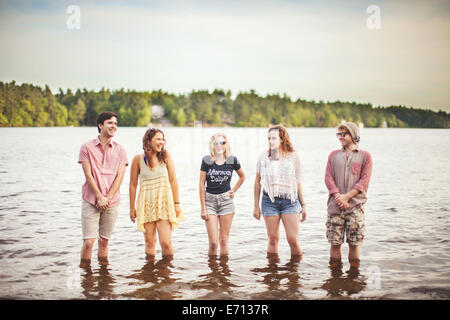 Five friends standing in water - Stock Photo