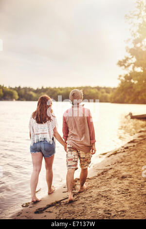 Young couple walking on beach holding hands - Stock Photo