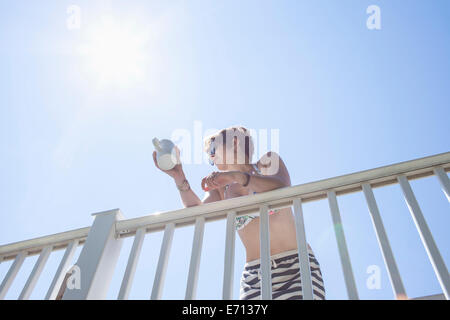 Low angle view of mid adult woman leaning against balcony with coffee mug - Stock Photo